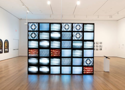 Adrian Piper, Mauer, 2010. Video Installation: Fernsehmonitore, Videos mit zufällig pro- grammierten Bildern, frische Rosen. Format variabel. Installa- tionsansicht: Adrian Piper: A Synthesis of Intuitions, 1965- 2016, Museum of Modern Art, New York, März-Juli 2018. Sammlung Adrian Piper Research Archive Foundation Berlin